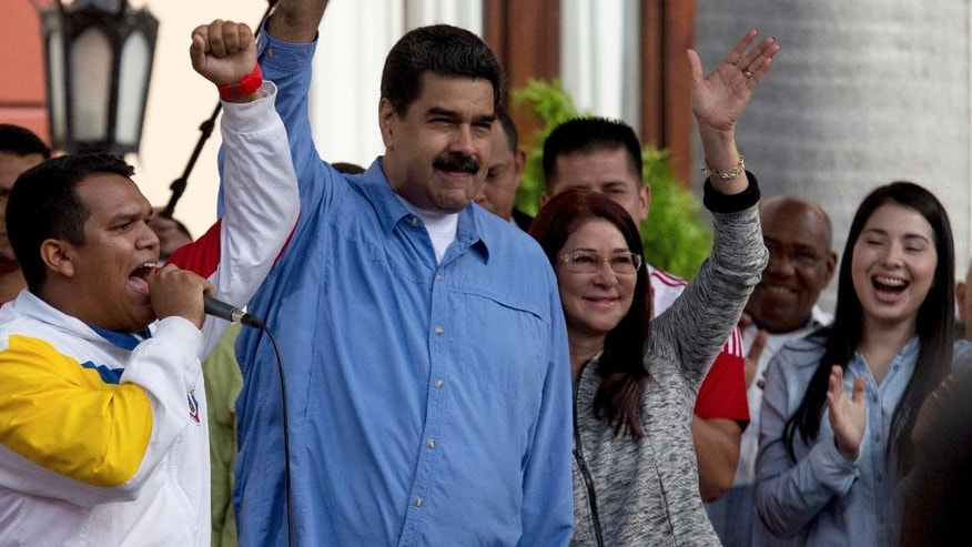 Venezuela's President Nicolas Maduro, center left, and his wife Cilia Flores, center right, greet supporters upon their arrival for a meeting with students to mark National Student Day, outside of Miraflores Presidential Palace in Caracas, Venezuela, Monday, Nov. 21, 2016.  (AP Photo/Fernando Llano)