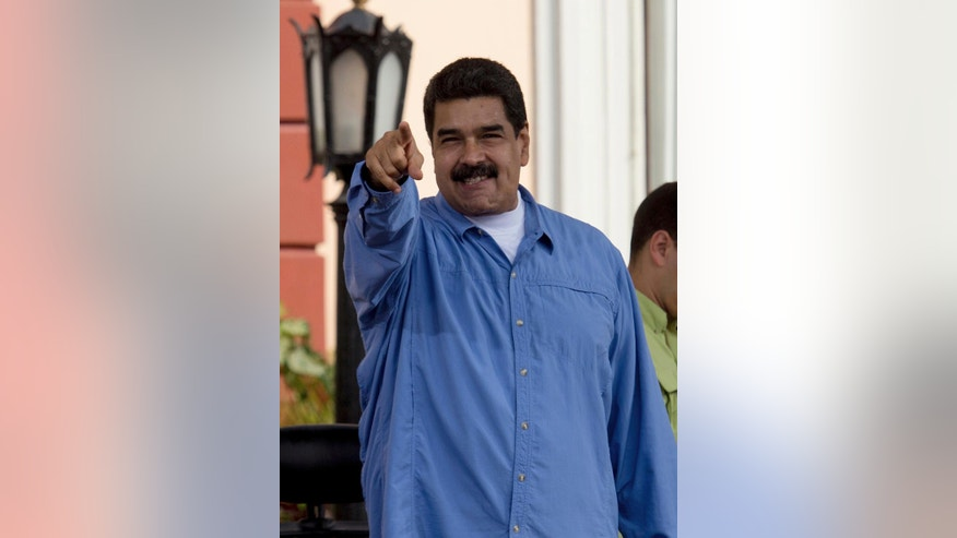 Venezuela's President Nicolas Maduro greets his supporters upon his arrival for a meeting with students outside of Miraflores Presidential Palace to mark national Student Day in Caracas, Venezuela, Monday, Nov. 21, 2016. (AP Photo/Fernando Llano)