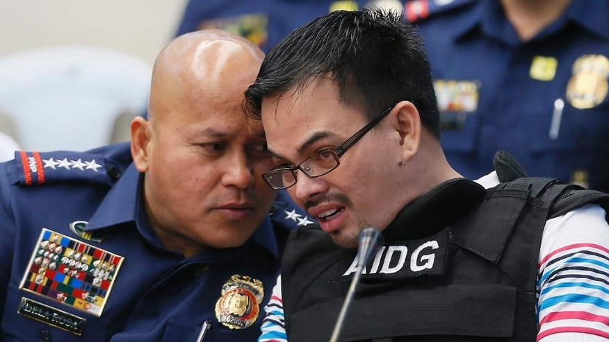 "Wearing a bullet-proof vest, alleged Filipino drug lord Rolando ""Kerwin"" Espinosa Jr., right, confers with Philippine National Police Chief Gen. Ronald ""Bato"" Dela Rosa, as he testifies during the resumption of the Senate probe into alleged extra-judicial killings in President Rodrigo Duterte's drug war, Wednesday, Nov. 23, 2016 in Pasay city, south of Manila, Philippines. The probe was called following the killing of Espinosa's father, local township Mayor Rolando Espinosa, by police while inside his jail. At left is Philippine National Police Chief Ronald ""Bato"" Dela Rosa. (AP Photo/Bullit Marquez)"