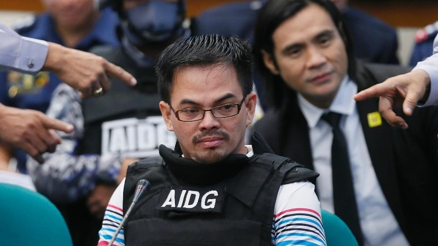 "Wearing a bullet-proof vest, Filipino self-confessed drug dealer Rolando ""Kerwin"" Espinosa Jr. prepares to testify on his involvement in the illegal drug trade in the country during the resumption of the Senate probe on alleged extra-judicial killings in President Rodrigo Duterte's drug war Wednesday, Nov. 23, 2016 in suburban Pasay city, south of Manila, Philippines. Espinosa, whose father was killed in an alleged gun fight in prison, has testified before a Philippine Senate investigation that he provided police officials and an opposition senator millions of pesos in protection money. (AP Photo/Bullit Marquez)"