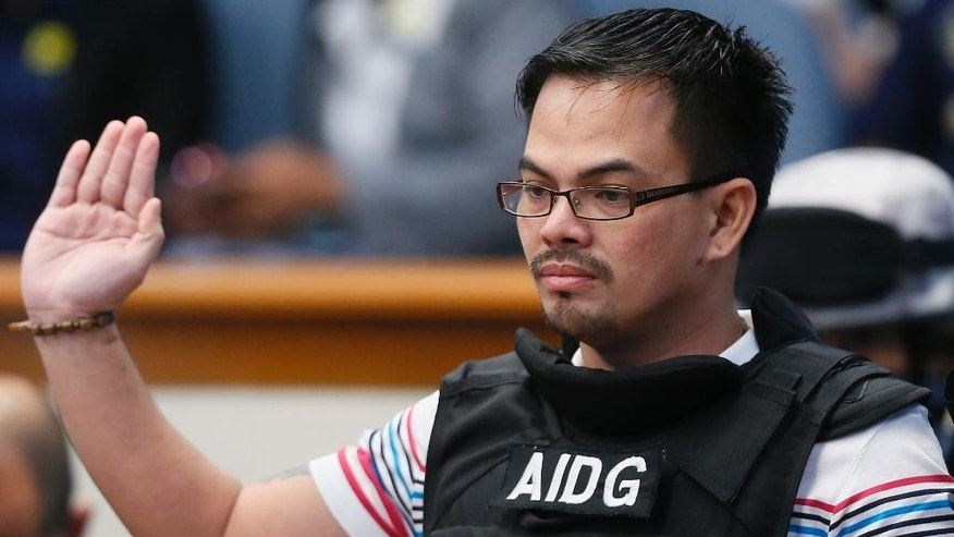 "Wearing a bullet-proof vest, Filipino self-confessed drug dealer Rolando ""Kerwin"" Espinosa Jr. takes his oath before testifying on his involvement in the illegal drug trade in the country at the resumption of the Senate probe on alleged extra-judicial killings in President Rodrigo Duterte's drug war Wednesday, Nov. 23, 2016 in suburban Pasay city, south of Manila, Philippines. Espinosa, whose father was killed in an alleged gun fight in prison, has testified before a Philippine Senate investigation that he provided police officials and an opposition senator millions of pesos in protection money. (AP Photo/Bullit Marquez)"