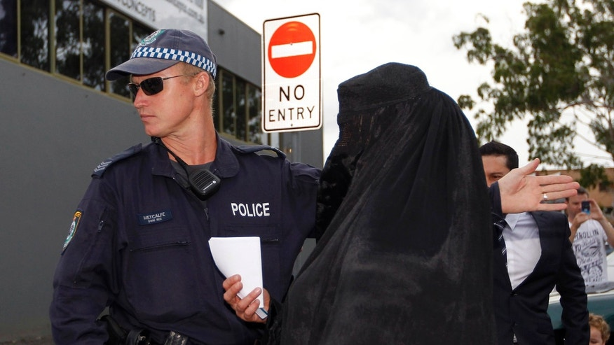 A police officer gestures to a woman wearing a burqa near the venue where controversial Dutch member of parliament Geert Wilders will speak in the Sydney suburb of Liverpool