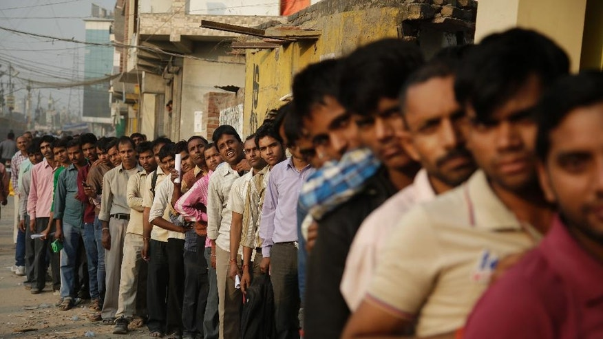 FILE - In this Nov. 13, 2016 file photo, Indians stand in a queue to deposit and exchange discontinued currency notes outside a bank in New Delhi, India. Indian prime minister Narendra Modi, in his Nov. 8 televised address, announced the demonetization of India's 500 and 1,000-rupee notes, which made up 86 percent of the country's currency. He said it would wipe out rampant corruption, though in a country of 1.3 billion where most people don't have bank accounts, it also wiped out legally collected savings. There are doubts about whether the demonetization drive will truly make an impact on corruption and tax evasion as many of those possessing piles of black money have come up with ways to save much of it without drawing government attention. Some have bought gold, sending gold prices soaring. Some were buying U.S. dollars or euros. Some have used cash for down payments on new apartments, with obliging real estate firms back-dating the invoices to before the currency overhaul. (AP Photo/Altaf Qadri, File)