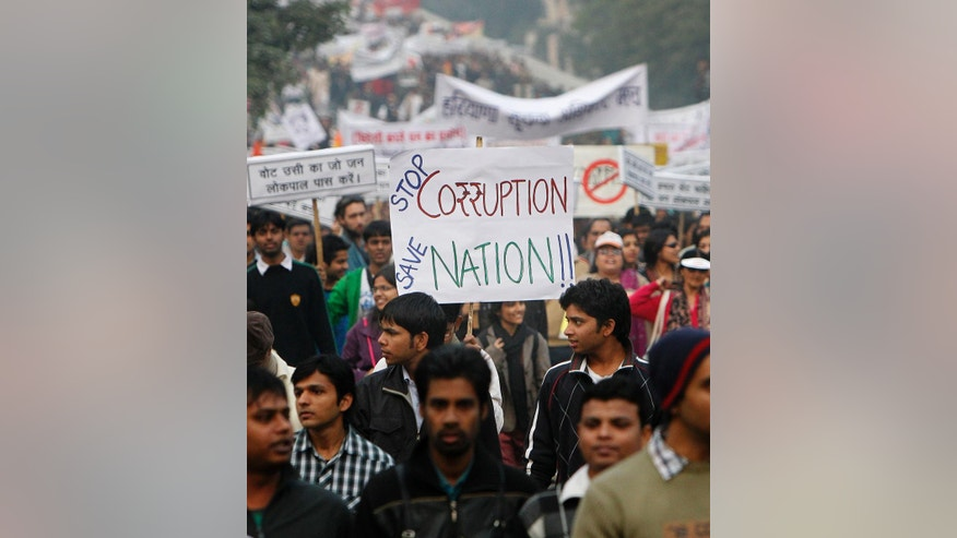 "FILE – In this Jan. 30, 2011 file photo, people hold placards and participate in a rally to protest against widespread corruption and poor governance in New Delhi, India. On Nov. 8, 2016, Prime Minister Narendra Modi announced in a surprise nighttime TV address that all 500 and 1,000-rupee notes, worth about $7.50 and $15, would be withdrawn immediately from circulation, a move designed to fight corruption and target people who have been dodging taxes by holding immense stockpiles of cash, known in India as ""black money."" But many still believe the effort will fall short of its goals to end corruption and tax evasion. India's underground economy is simply too big, accounting for up to a quarter of the country's gross domestic product. (AP Photo/Gurinder Osan, File)"