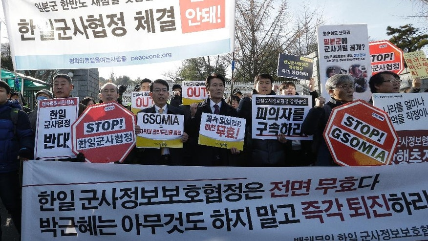 """South Korean protesters shout slogans during a rally to oppose the General Security of Military Information Agreement (GSOMIA) between South Korea and Japan, in front of the Defense Ministry in Seoul, South Korea, Wednesday, Nov. 23, 2016. South Korea's Cabinet on Tuesday approved an intelligence-sharing agreement with Japan to better deal with threats from North Korea, officials said. The signs read """"Stop, the General Security of Military Information Agreement (GSOMIA) between South Korea and Japan."""" (AP Photo/Ahn Young-joon)"""