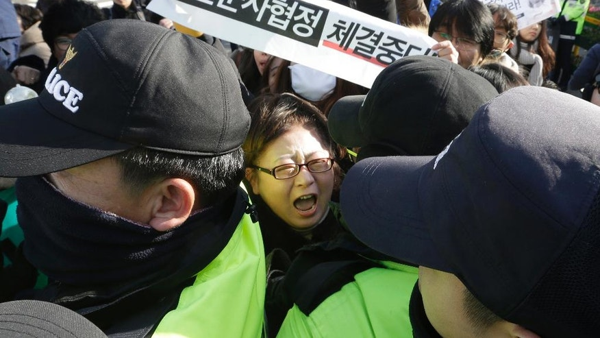 """A South Korean protester scuffles with police officers during a rally to oppose the General Security of Military Information Agreement (GSOMIA) between South Korea and Japan, in front of the Defense Ministry in Seoul, South Korea, Wednesday, Nov. 23, 2016. South Korea's Cabinet on Tuesday approved an intelligence-sharing agreement with Japan to better deal with threats from North Korea, officials said. The signs read """"Stop, the military agreement between South Korea and Japan."""" (AP Photo/Ahn Young-joon)"""