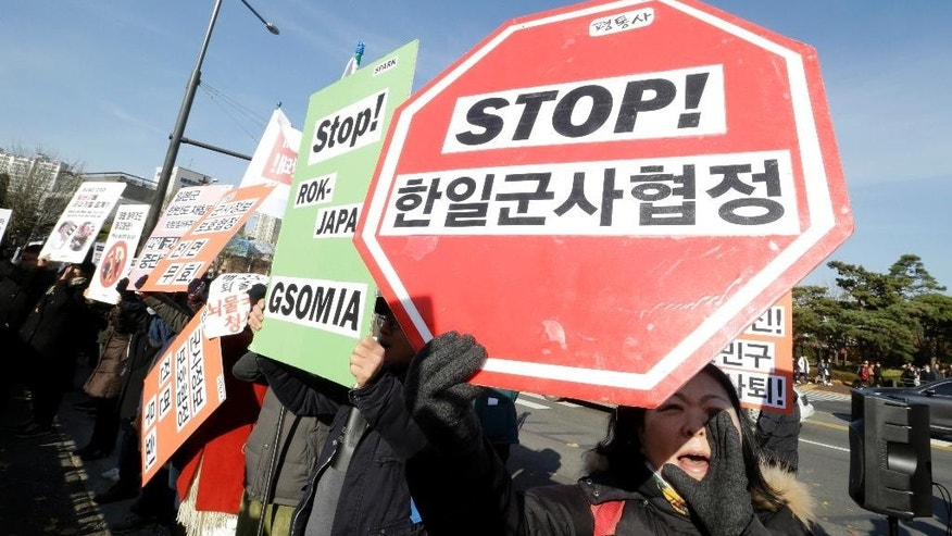 "South Korean protesters hold up their banners during a rally to oppose the General Security of Military Information Agreement (GSOMIA) between South Korea and Japan, in front of the Defense Ministry in Seoul, South Korea, Wednesday, Nov. 23, 2016. South Korea's Cabinet on Tuesday approved an intelligence-sharing agreement with Japan to better deal with threats from North Korea, officials said. The signs read ""Stop, the military agreement between South Korea and Japan."" (AP Photo/Ahn Young-joon)"