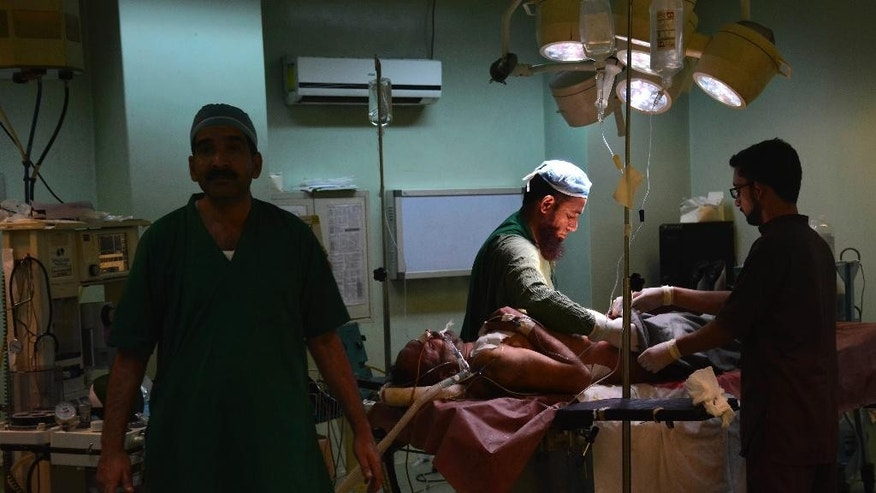 Pakistani doctors treat a villager injured by Indian firing, at a local hospital in Muzaffarabad, capital of Pakistani Kashmir, Wednesday, Nov. 23, 2016. Artillery fire and shelling from India targeted several villages and struck a passenger bus near the dividing line in the disputed region of Kashmir on Wednesday, killing many civilians wounding more than a dozen others, the Pakistani military and officials said. (AP Photo/M.D. Mughal)