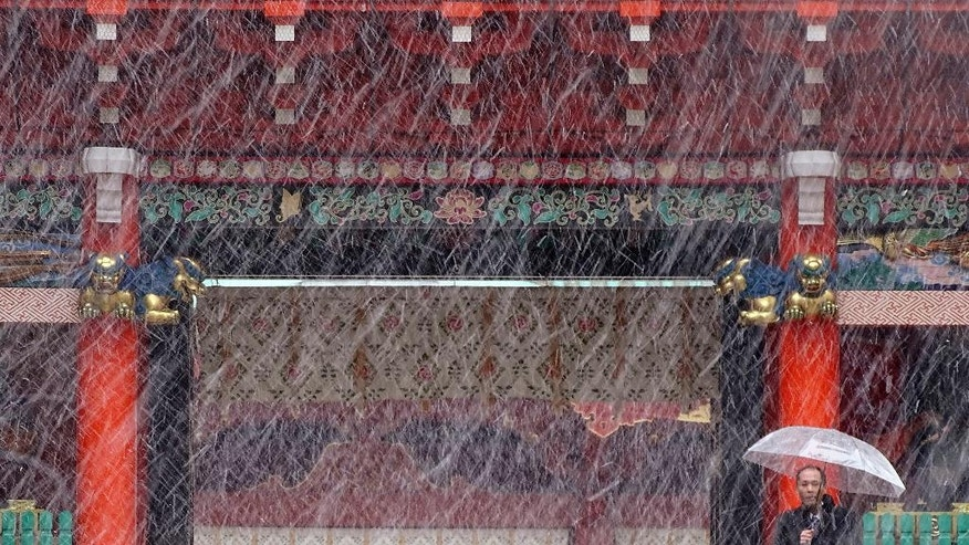 A man stands near the gate in the snow at Kanda Myojin shrine in Tokyo, Thursday, Nov. 24, 2016.  Tokyo residents have woken up to the first November snowfall in more than 50 years. An unusually cold air mass brought wet snow to Japan's capital on Thursday. Above-freezing temperatures kept the snow from sticking, but forecasters said there could be an accumulation of up to 2 centimeters (1 inch). The last time it snowed in central Tokyo in November was in 1962. (AP Photo/Eugene Hoshiko)
