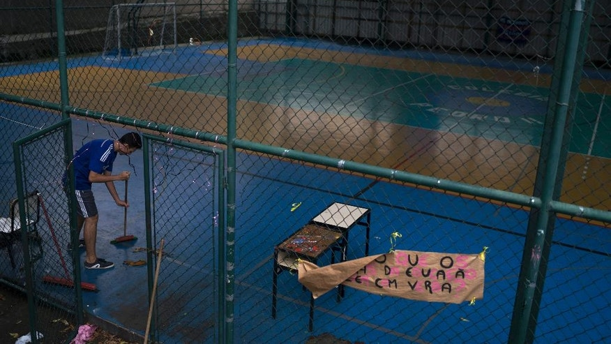 In this Nov. 18, 2016 photo, a student sweeps the gym during a student occupation of his high school, Colegio Pedro II, aimed at protesting education reform and austerity measures in Rio de Janeiro, Brazil. Students are against a government proposed education bill would make optional subjects that had previously been required, like arts and physical education, and would also lengthen the school day. (AP Photo/Leo Correa)