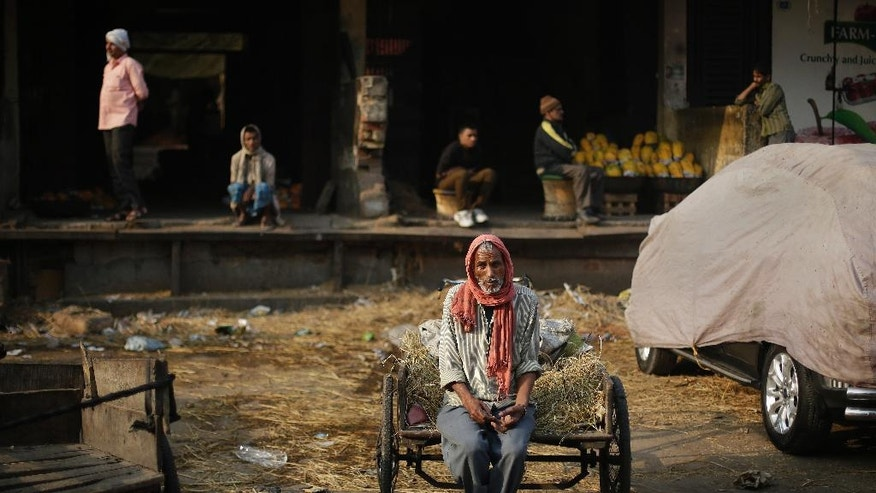 """In this Friday, Nov. 18, 2016 photo, a laborer sits on his cart waiting for work at Azadpur Mandi, one of Asia's largest wholesale market for fruits and vegetables in New Delhi, India. Business at the massive New Delhi market is evaporating, the food spoiling and wasted, two weeks after the government's surprise currency move made more than 80 percent of India's banknotes useless. By withdrawing all 500- and 1,000-rupee notes from circulation, the government is trying to clean India's economy of """"black money,"""" or untaxed wealth. Its success remains to be seen, but for now the move has created serpentine queues outsides banks and ATMs of people replacing their rupee notes or making small withdrawals. (AP Photo/Altaf Qadri)"""