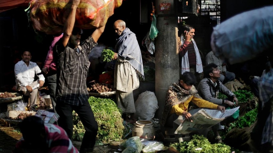 In this Friday, Nov. 18, 2016 photo, a laborer carries a sackful of vegetables at Azadpur Mandi, one of Asia's largest wholesale market for fruits and vegetables in New Delhi, India. The scale of India's cash economy can be seen in this market. Almost every transaction, like most in India, is done in cash. And business at the massive New Delhi market is evaporating, the food spoiling and wasted, two weeks after the government's surprise currency move made more than 80 percent of India's banknotes useless. (AP Photo/Altaf Qadri)