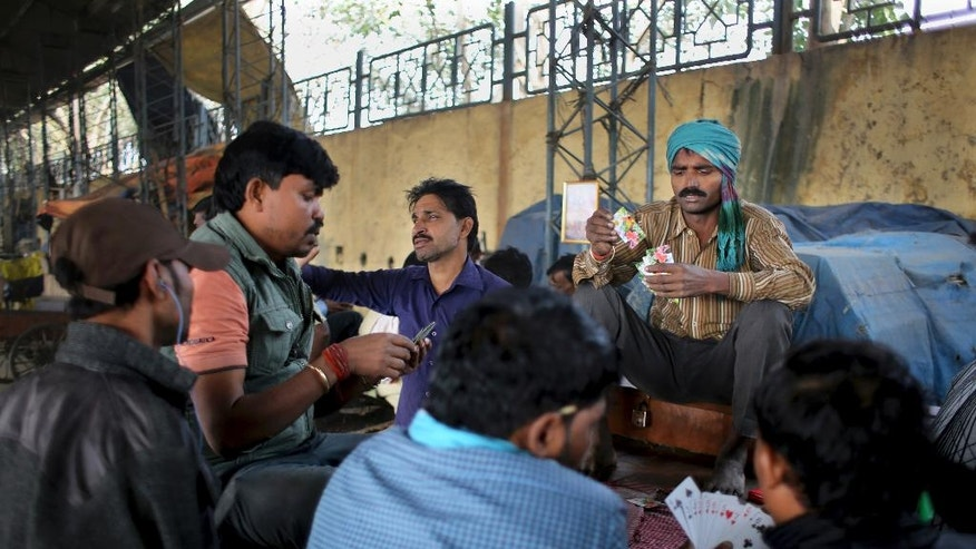 In this Friday, Nov. 18, 2016 photo, labourers and other workers play cards at Azadpur Mandi, one of Asia's largest wholesale market for fruits and vegetables in New Delhi, India. The scale of India's cash economy can be seen in this market. Almost every transaction, like most in India, is done in cash. And business at the massive New Delhi market is evaporating, the food spoiling and wasted, two weeks after the government's surprise currency move made more than 80 percent of India's banknotes useless. (AP Photo/Altaf Qadri)