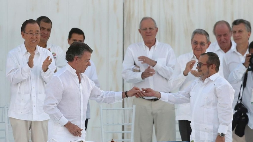 FILE - In this Sept. 26, 2016, file photo, Colombia's President Juan Manuel Santos, front left, gives a peace pin to the top commander of the Revolutionary Armed Forces of Colombia, FARC, Rodrigo Londono, known by the alias Timochenko after they signed a peace agreement between the government and the FARC in Cartagena, Colombia. With less fervor and an added dose of uncertainty Colombia's government will sign Thursday, Nov. 24, for the second time in under two months, a peace accord with the country's largest rebel group.. (AP Photo/Fernando Vergara, File)