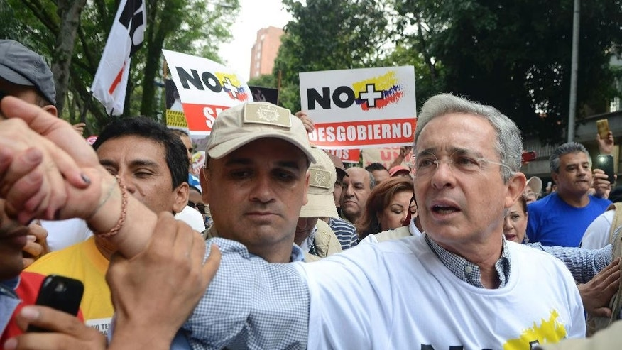 FILE - In this April 2, 2016, file photo, opposition leader and former President Alvaro Uribe shakes hands with a supporter as he takes part in a protest against President Juan Manuel Santos' government and to denounce the concessions the government has made in peace talks with the Revolutionary Armed Forces of Colombia, or FARC, in Medellin, Colombia. Uribe has managed to influence the new peace accord to be signed on Thursday, Nov. 24, with changes that range from a prohibition on foreign magistrates who will judge FARC crimes to a commitment from the insurgents to forfeit assets, some of them amassed through drug-trafficking, to help compensate their victims.. (AP Photo/Luis Benavides, File)