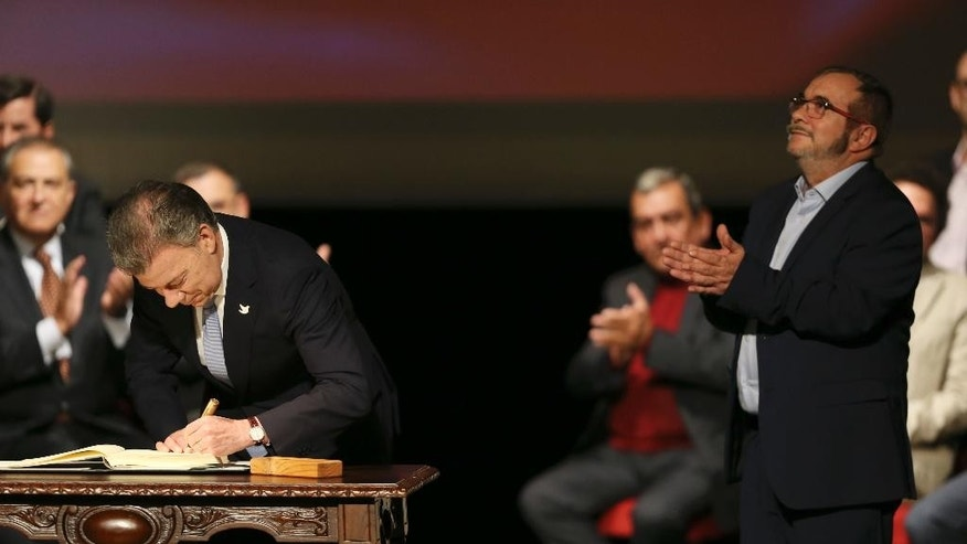 Colombia's President Juan Manuel Santos signs a modified peace accord with rebels of the Revolutionary Armed Forces of Colombia, FARC, as rebel top leader Rodrigo Londono, known and Timochencko, right, applauds, at Colon Theater in Bogota, Colombia, Thursday, Nov. 24, 2016. An original accord ending the half century conflict was rejected by voters in a referendum last month. (AP Photo/Fernando Vergara)