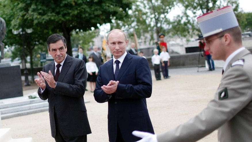 "FILE - In this Tuesday June 21, 2011file picture, French Prime Minister Francois Fillon, left, and his Russian counterpart Vladimir Putin, center, stand side by side during the inauguration of a monument dedicated to the collaboration between the French and Russian Armies during the Second World War, in Paris, France. Francois Fillon, who polls suggest is the frontrunner, wants to end sanctions against Russia over its actions in Ukraine, work with Russia to fight the Islamic State group, and insists ""Russia poses no threat to the West."" (AP Photo/Thibault Camus, File)"