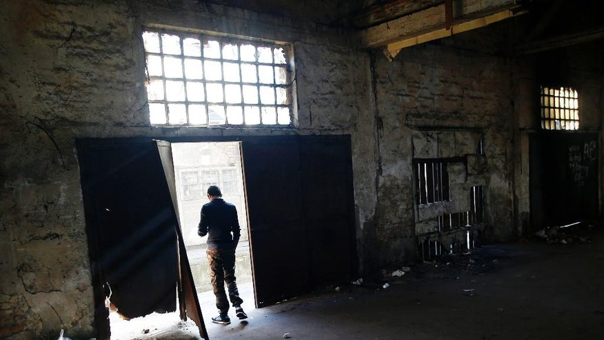 A migrant stands in the doorway of an abandoned warehouse in Belgrade, Serbia, Wednesday, Nov. 23, 2016. About 1,000 migrants occupied the rubbish-strewn sprawling complex in search for protection from cold and rain. (AP Photo/Darko Vojinovic)