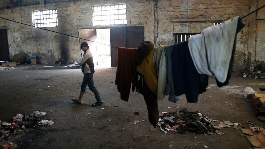 A migrant walks inside an abandoned warehouse in Belgrade, Serbia, Wednesday, Nov. 23, 2016. About 1,000 migrants occupied the rubbish-strewn sprawling complex in search for protection from cold and rain. (AP Photo/Darko Vojinovic)