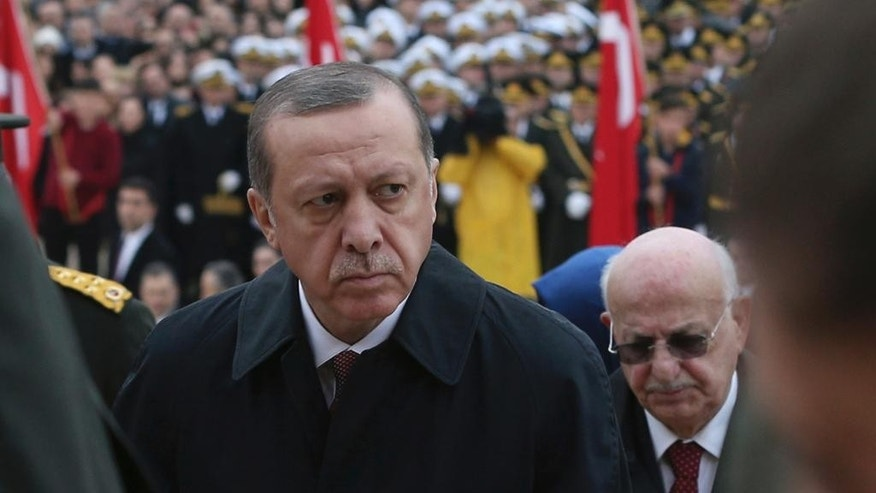 In this Oct. 29, 2016 file photo, Turkish President Recep Tayyip Erdogan, center, follows a military honour guard walking to the mausoleum of Turkey's founder Mustafa Kemal Ataturk on Republic Day in Ankara, Turkey. Since quashing a July coup attempt, Turkey's president has used extraordinary powers from a state of emergency to arrest and purge thousands of opponents. Recep Tayyip Erdogan has also vowed to back public demands to reinstate the death penalty and suggested submitting Turkey's long-sought goal of European Union membership to a referendum. (AP Photo/Burhan Ozbilici/File)