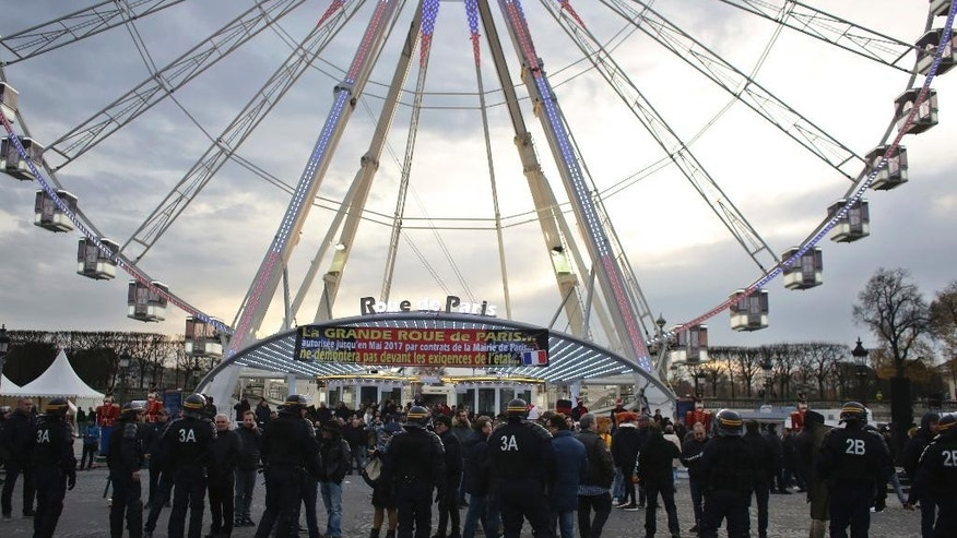 "Fair workers block a central Paris interchange to protest government orders to remove a giant Ferris, in Paris, Thursday, Nov. 24, 2016. About 100 workers parked dozens of large trucks on the Place de la Concorde early Thursday beneath the ""Roue de Paris"" amusement park ride. (AP Photo/Thibault Camus)"