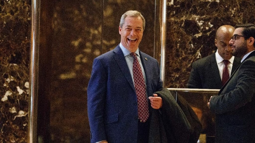 """FILE - In this Saturday, Nov. 12, 2016, file photo, U.K. Independence Party leader Nigel Farage smiles as he arrives at Trump Tower, in New York. Farage, the interim leader of the U.K. Independence Party, says he is """"flattered"""" by Donald Trump's suggestion that he become Britain's ambassador to the United States. Farage said Tuesday he would do anything possible to help relations between the two countries even as Prime Minister Theresa May's office said Britain already has an ambassador in place in Washington. (AP Photo/ Evan Vucci, File)"""
