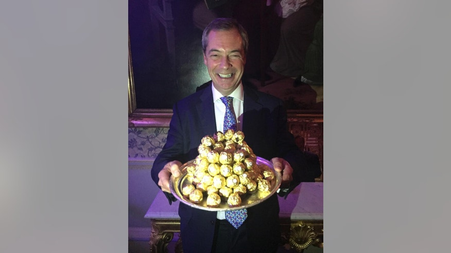 U.K. Independence Party leader Nigel Farage smiles after he was presented with a tray of Ferrero Rocher chocolates at an event to thank him for his contribution to Brexit, at an hotel in London late Wednesday Nov.  23, 2016. (Andrew Woodcock/PA via AP)