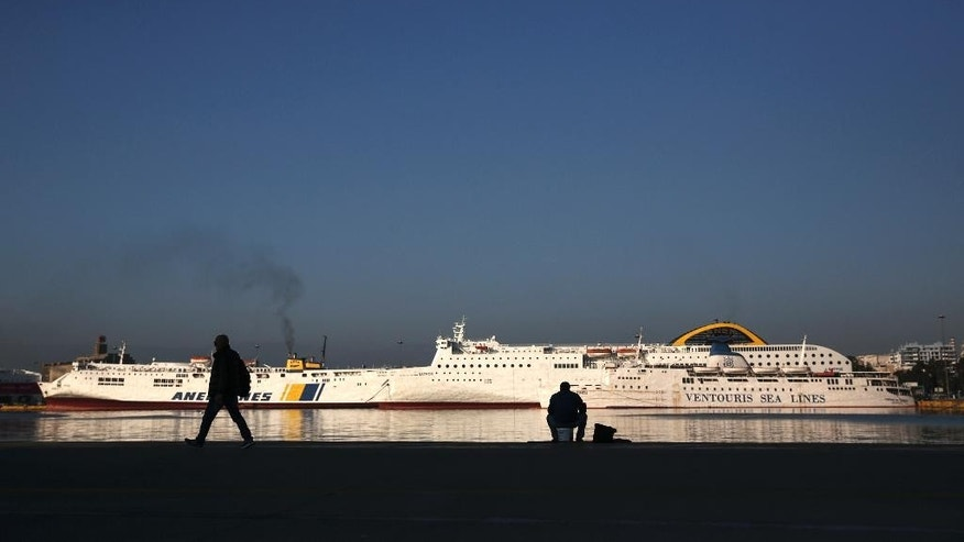 A man walks on a promenade in front of moored ferries during a seamen 24-hour strike at Piraeus port, near Athens, Thursday, Nov. 24, 2016. The country's largest civil servants union called a 24-hour strike for Thursday, arguing that mass staff cuts could not continue. (AP Photo/Yorgos Karahalis)