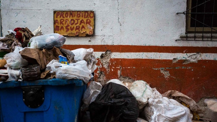 """In this Nov. 21, 2016 photo, garbage is piled up on a street beside a sign that reads in Spanish """"Forbidden to throw rubbish"""" in Havana, Cuba. Known for chaotic avenues filled with car-dodging pedestrians, balconies that discharge waterfalls onto sidewalks and reggaeton music played at deafening volume, Havana wants to clean up its streets. (AP Photo/Desmond Boylan)"""