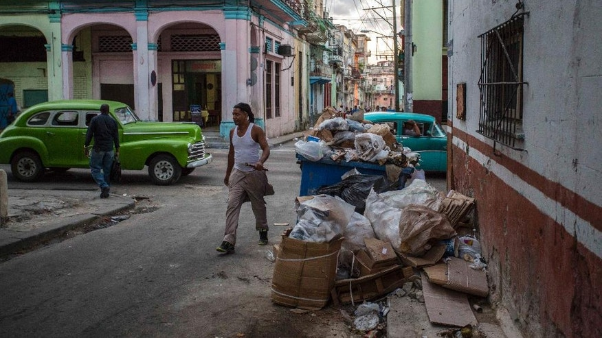 In this Nov. 21, 2016 photo, garbage is piled up on a street corner in Havana, Cuba. Known for chaotic avenues filled with car-dodging pedestrians, balconies that discharge waterfalls onto sidewalks and reggaeton music played at deafening volume, Havana wants to clean up its streets. (AP Photo/Desmond Boylan)