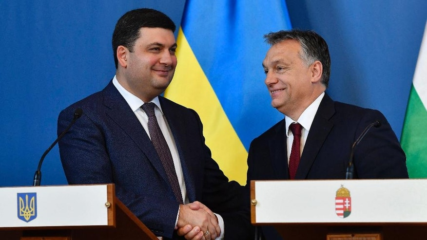 Ukranian Prime Minister Volodymyr Groysman, left, and Hungarian Prime Minister Viktor Orban shake hands during their press conference after their negotiations in the Parliament building in Budapest, Hungary, Thursday, Nov. 24, 2016. (Tibor Illyes/MTI via AP)