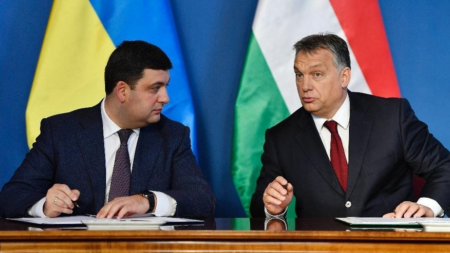 Ukranian Prime Minister Volodymyr Groysman, left, and Hungarian Prime Minister Viktor Orban sign a cooperation agreement after their negotiations in the Parliament building in Budapest, Hungary, Thursday, Nov. 24, 2016. (Tibor Illyes/MTI via AP)