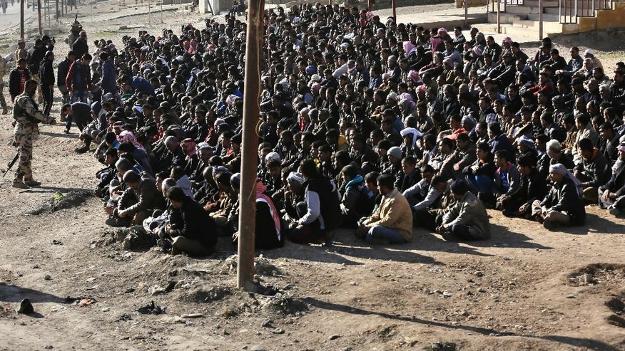 Scores of Iraqi male residents are rounded up by the Iraqi army in Gogjali neighborhood, in Mosul, Iraq, Thursday, Nov. 24, 2016.  Iraqi forces urged them to come out with information of any Islamic State members among them. An Iraqi officer addressed the group, demanding to know the whereabouts of alleged IS militants who opened fire on troops a few days earlier. (AP Photo/Hussein Malla)