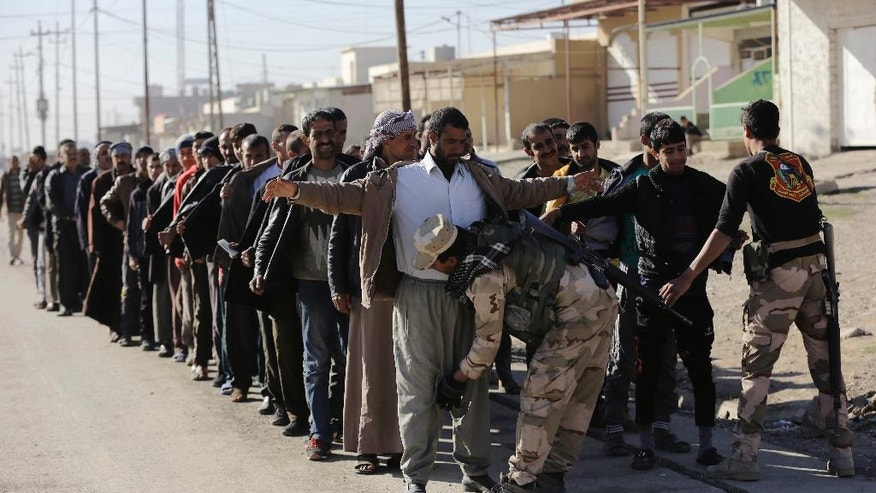 Iraqi soldiers search scores of Iraqi male residents who were rounded up by Iraqi forces in Gogjali neighborhood, in Mosul, Iraq, Thursday, Nov. 24, 2016. Iraqi forces urged them to come out with information of any Islamic State members among them. An Iraqi officer addressed the group, demanding to know the whereabouts of alleged IS militants who opened fire on troops a few days earlier. (AP Photo/Hussein Malla)