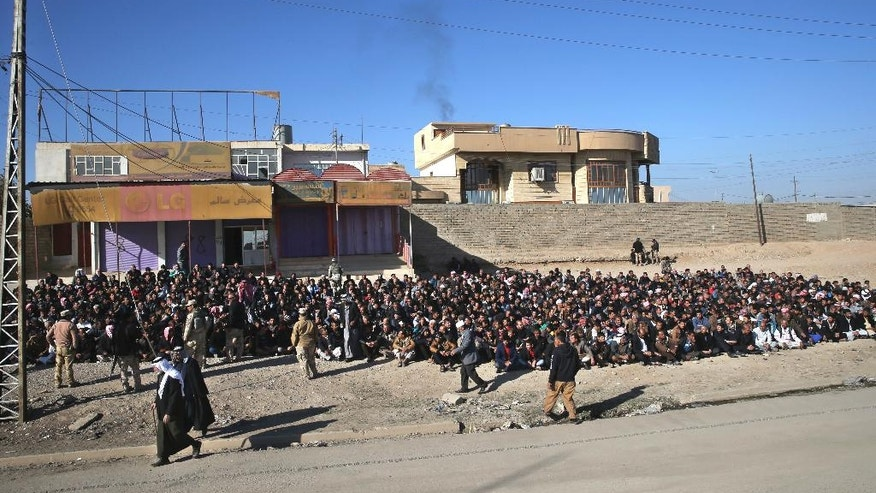 Scores of Iraqi male residents are rounded up by the Iraqi forces in Gogjali neighborhood, in Mosul, Iraq, Thursday, Nov. 24, 2016.  Iraqi forces urged them to come out with information of any Islamic State members among them. An Iraqi officer addressed the group, demanding to know the whereabouts of alleged IS militants who opened fire on troops a few days earlier. (AP Photo/Hussein Malla)