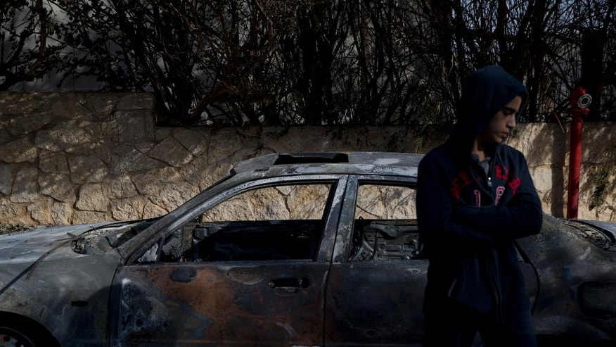 A boy stands next to a burnt car following a wildfire in Zikhron Ya'akov, Israel, Wednesday, Nov. 23, 2016.  Due to dry conditions, wildfires broke out for the second day in Israel. In Zikhron Ya'akov around ten homes were burned and several people sustained light injuries from smoke inhalation. (AP Photo/Ariel Schalit)
