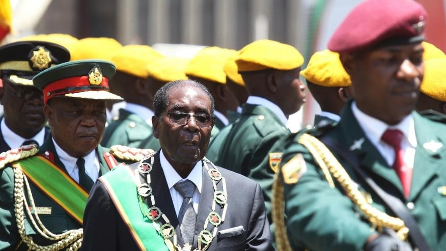 FILE -- In this Oct. 6, 2016 file photo Zimbabwean President Robert Mugabe, centre, inspects the guard of honour during the opening of the 4th session of the 8th Parliament of Zimbabwe in Harare. In the country, more vendors demand cash payments, the economy looks more vulnerable than ever and the increasingly frail Mugabe, talks ambiguously of retiring as his 93rd birthday approaches. (AP Photo/Tsvangirayi Mukwazhi - File)
