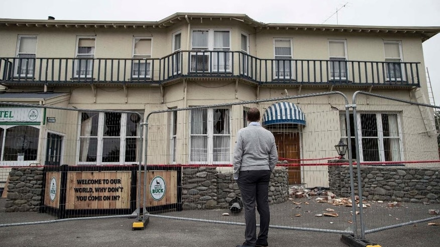 New Zealand Prime Minister John Key inspects damage to the Waiau Lodge Hotel in Waiau, New Zealand, on Thursday, Nov. 24, 2016, after a magnitude 7.8 earthquake hit the region 10 days earlier. The quake killed two people and created landslides that have blocked a major coastal highway. (Iain McGregor/Christchurch Press/Pool via AP)