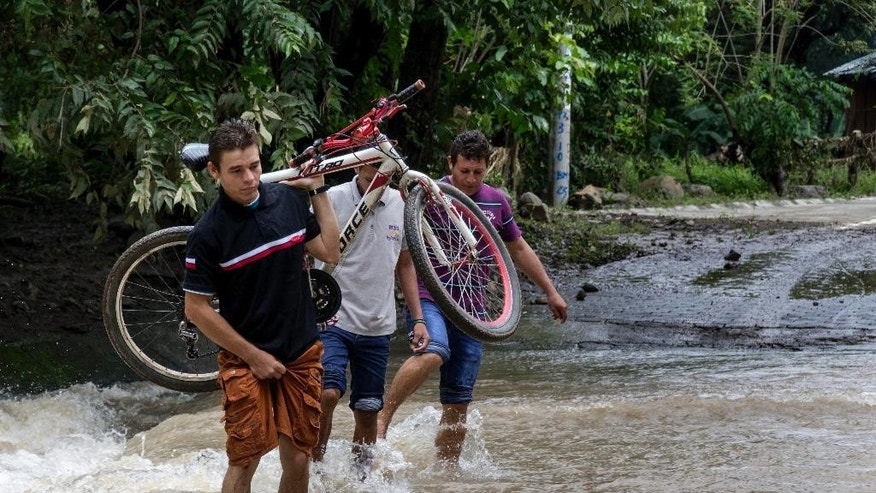 A young man carries his bicycle across a road that flooded after the passing of Hurricane Otto in Cardenas, Nicaragua, Friday, Nov. 25, 2016. Otto made landfall on Nicaragua's Caribbean coast on Thursday as a dangerous Category 2 storm but it faded to tropical storm force before emerging over the eastern Pacific early Friday.  (AP Photo/Miguel Alvarez)