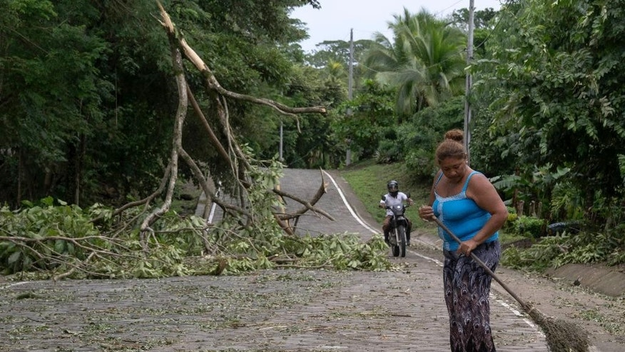 A woman sweeps the street partially blocked by a fallen tree branch after the passing of Hurricane Otto in Cardenas, Nicaragua, Friday, Nov. 25, 2016. Otto made landfall on Nicaragua's Caribbean coast on Thursday as a dangerous Category 2 storm but it faded to tropical storm force before emerging over the eastern Pacific early Friday. (AP Photo/Miguel Alvarez)