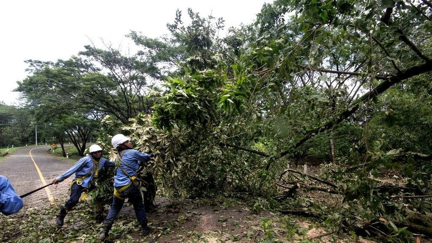 Power company workers cut a tree branch that fell during the passing of Hurricane Otto in Cardenas, Nicaragua, Friday, Nov. 25, 2016. Otto made landfall on Nicaragua's Caribbean coast on Thursday as a dangerous Category 2 storm but it faded to tropical storm force before emerging over the eastern Pacific early Friday.  (AP Photo/Miguel Alvarez)