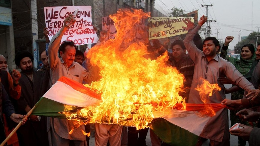 Pakistan protesters burn a representation of an Indian flag to condemn recent firing at the Line of Control, in Multan, Pakistan, Wednesday, Nov. 23, 2016. Artillery fire and shelling from India targeted several villages and struck a passenger bus near the dividing line in the disputed region of Kashmir on Wednesday, killing many civilians wounding more than a dozen others, the Pakistani military and officials said. (AP Photo/Mohammad Asim)