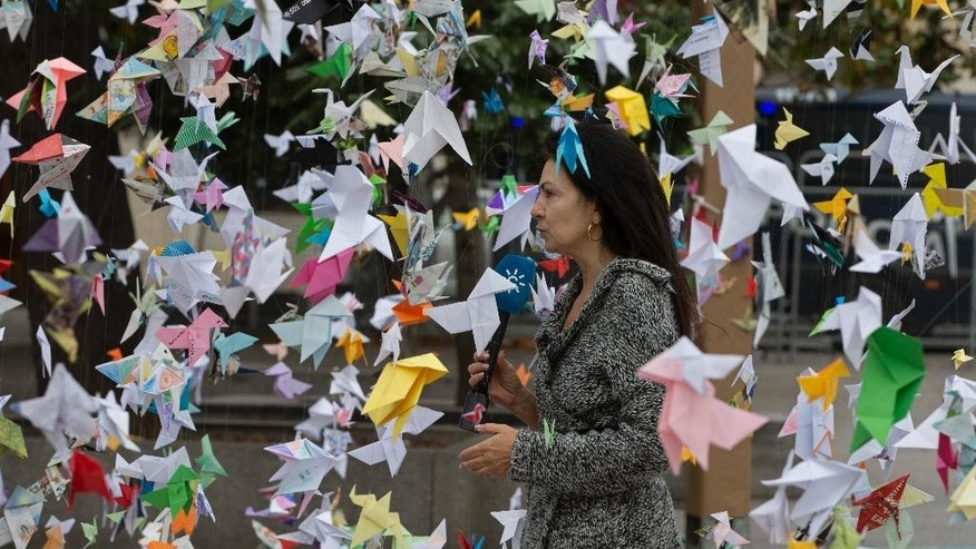 A TV journalist stands in the middle of paper birds hanging on strings outside the Spanish Parliament in Madrid, Spain, Thursday, Nov. 24, 2016. Environmentalists have displayed hundreds of colored origami paper birds outside the Parliament to demand greater government action to protect Spain's Donana National Park, one of Europe's most celebrated conservation wetlands, which they say is in danger of being placed on UNESCO's endangered list due to a grave risk from excessive water extraction. (AP Photo/Paul White)