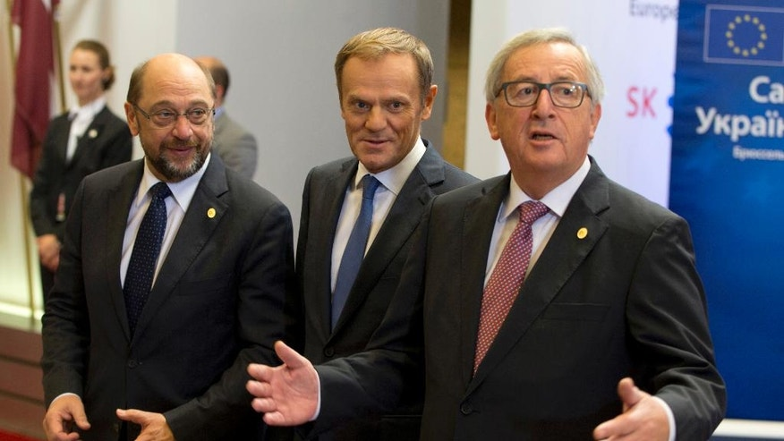 European Council President Donald Tusk, center, European Parliament President Martin Schultz, left, and European Commission President Jean-Claude Juncker, right, speak with the media during arrivals for an EU-Ukraine summit at the European Council building in Brussels on Thursday, Nov. 24, 2016. (AP Photo/Virginia Mayo)