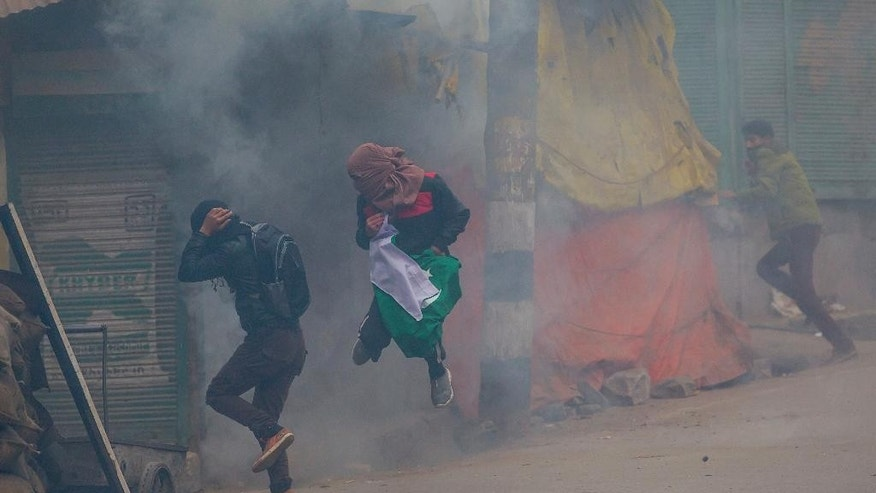 Kashmiri Muslim protester, center, holds a Pakistani flag and jumps to avoid tear gas shell fired by Indian policemen during a protest after Friday prayers near the main mosque, Jamia Masjid, after authorities allowed Friday prayers for the first time in more than four months in Srinagar, Indian controlled Kashmir, Friday, Nov. 25, 2016. Government forces have prevented worshippers from offering Friday prayers at large mosques for the past 19 weeks amid the biggest protests against Indian rule in recent years, sparked by the killing in July of a popular rebel commander by Indian soldiers. (AP Photo/Dar Yasin)