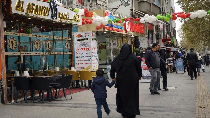"People walk in the Fatih district in Istanbul, Wednesday, Nov. 16, 2016. With its colorful signs, flashing lights and awnings displaying Arabic script, Istanbul's Aksaray neighborhood has been dubbed ""Little Syria."" But a regulation forcing businesses to remove Arabic and other non-Latin script from shop signs now portends an end to the distinctively Arabic feel of the district that is dotted with Syrian-run businesses and restaurants. (AP Photo/ Neyran Elden)"