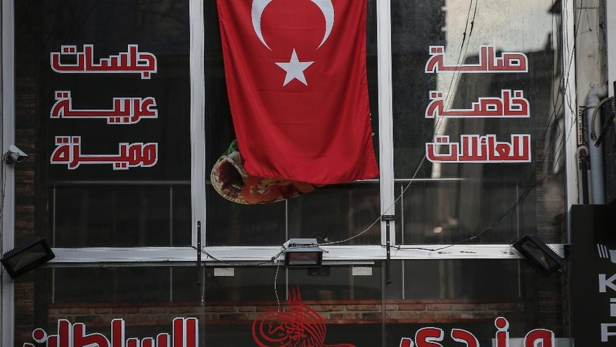 "The window of a shop in the Fatih district in Istanbul, Wednesday, Nov. 23, 2016. With its colorful signs, flashing lights and awnings displaying Arabic script, Istanbul's Aksaray neighborhood has been dubbed ""Little Syria."" But a regulation forcing businesses to remove Arabic and other non-Latin script from shop signs now portends an end to the distinctively Arabic feel of the district that is dotted with Syrian-run businesses and restaurants. (AP Photo/Emrah Gurel)"
