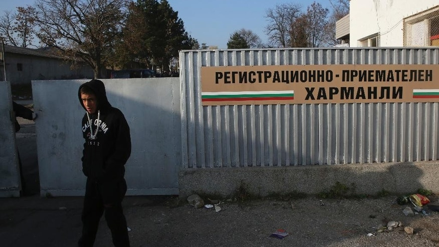 A local boy walks  near the fence of the Harmanli registration center as Bulgarian army soldiers are deployed in Harmanli, Bulgaria on Friday, Nov. 25, 2016. Some 400 migrants have been detained after clashes with police at a refugee camp in southern Bulgaria, that left several injured. Another 15 migrants have been arrested for damaging property, police said on Friday.(AP Photo/Visar Kryeziu)