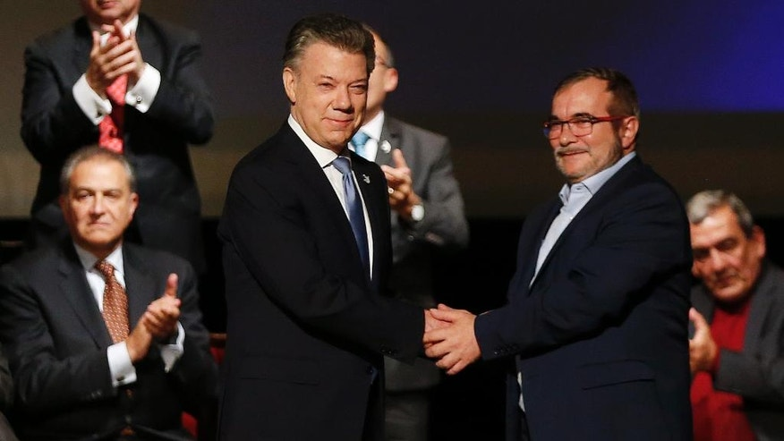 Colombia's President Juan Manuel Santos, left, shakes hands with Rodrigo Londono, known as Timochenko, top leader of the Revolutionary Armed Forces of Colombia, FARC, after signing a revised peace pact at Colon Theater in Bogota, Colombia, Thursday, Nov. 24, 2016. An original accord ending the half century conflict was rejected by voters in a referendum last month. (AP Photo/Fernando Vergara)