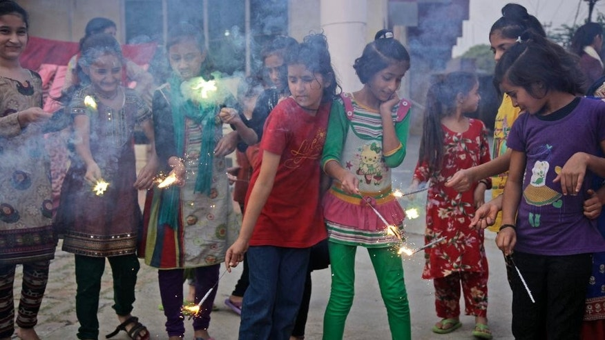 FILE - In this Oct. 29, 2016 file photo, children play with firecrackers on the eve of Diwali, the Hindu festival of lights, at an orphanage in Jammu, India. India's top court on Friday, Nov. 25, stopped firecracker sales in and around New Delhi as the worst season for air pollution begins. The fireworks set off during the Hindu festival of Diwali in September caused measurements of tiny lung-clogging particulate matter PM 2.5 to reach dangerous levels above 300 micrograms per cubic meter. (AP Photo/Channi Anand)